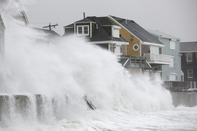 Waves crash over houses in Massachusetts as a major winter storm strikes the US east coast