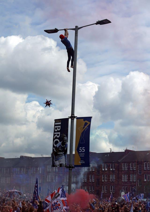 A Rangers fan clings on to a lamp post outside Ibrox
