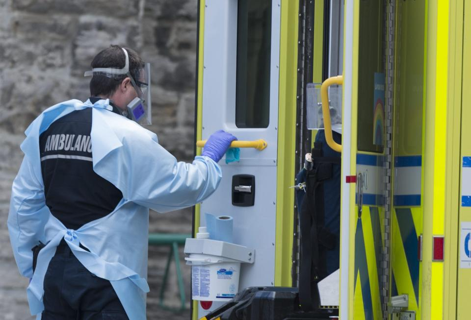 A paramedic wipes down the door of an ambulance outside a hospital in Montreal (Credit: Graham Hughes/The Canadian Press)