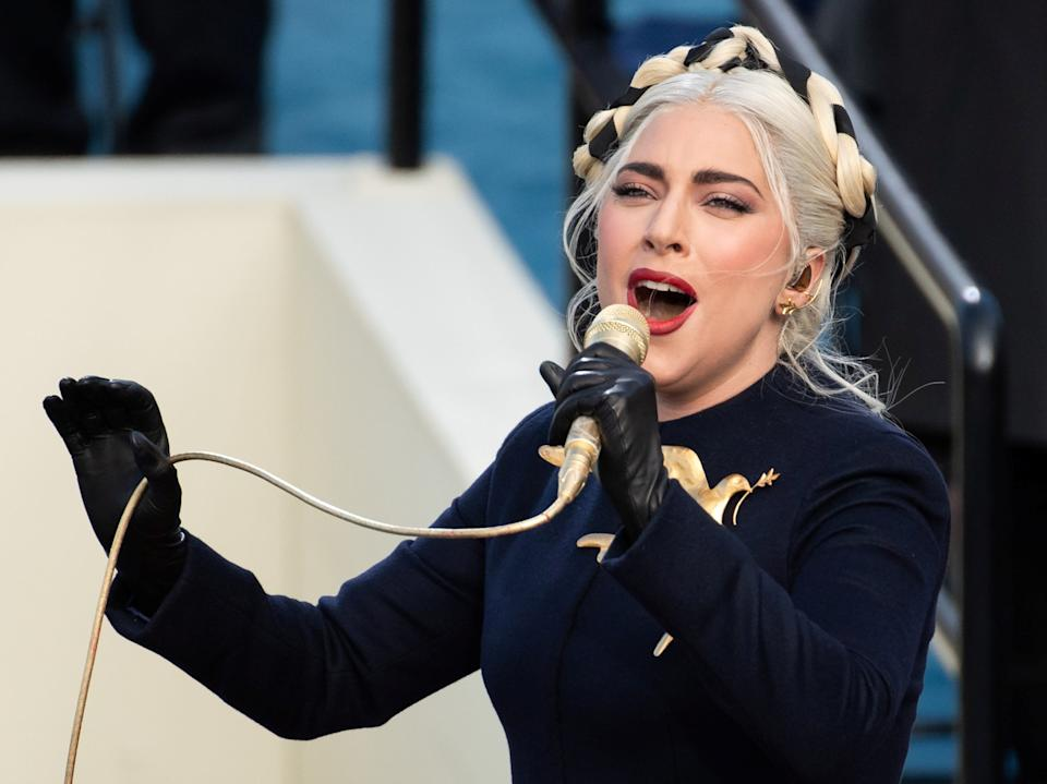 Lady Gaga sings the National Anthem during the inauguration ceremony dressed in a custom Schiaparelli Haute Couture look that featured a gilded dove of peace broochREUTERS