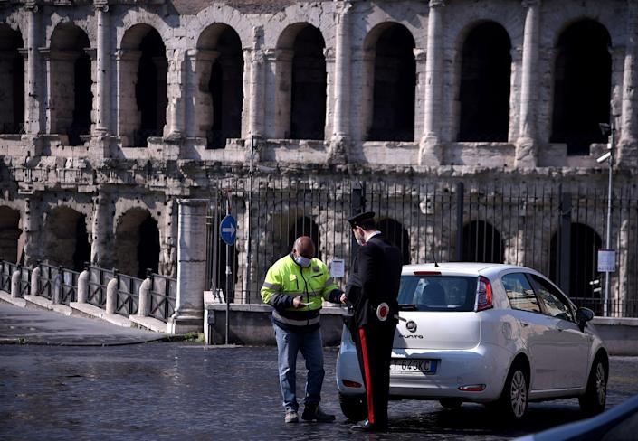 Image: An Italian Carabiniere controls a driver by the Teatro di Marcello in Rome on April 8, 2020 during the country's lockdown aimed at curbing the spread of the COVID-19, caused by the novel coronavirus. (Filippo Monteforte / AFP - Getty Images)