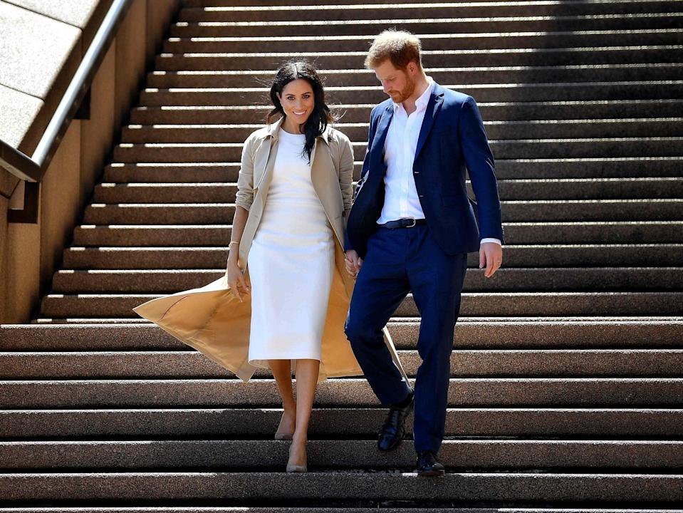 <p>In this file photo taken on October 16, 2018 Britain's Prince Harry and his wife Meghan walk down the stairs of the iconic Opera House in Sydney.</p> (AFP via Getty Images)
