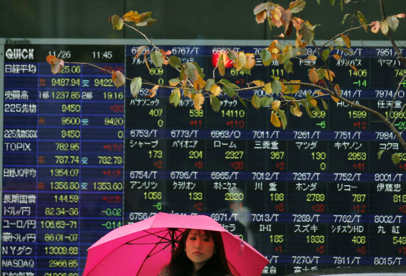 A woman stands in the rain in front of an electronic stock board of a securities firm in Tokyo, Monday, Nov. 26, 2012. Asian stock markets posted slight gains Monday after the unofficial start of the holiday shopping season in the U.S. topped expectations, offsetting concerns about Greece's financial crisis. (AP Photo/Koji Sasahara)