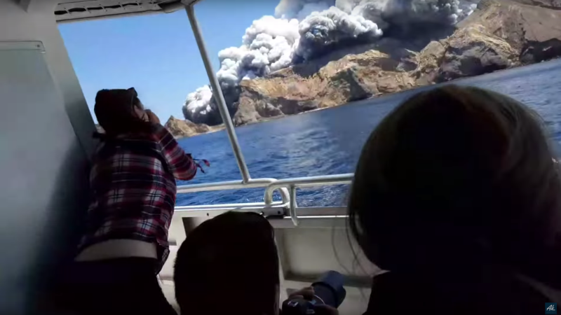 A tour group watches White Island erupt from a boat.