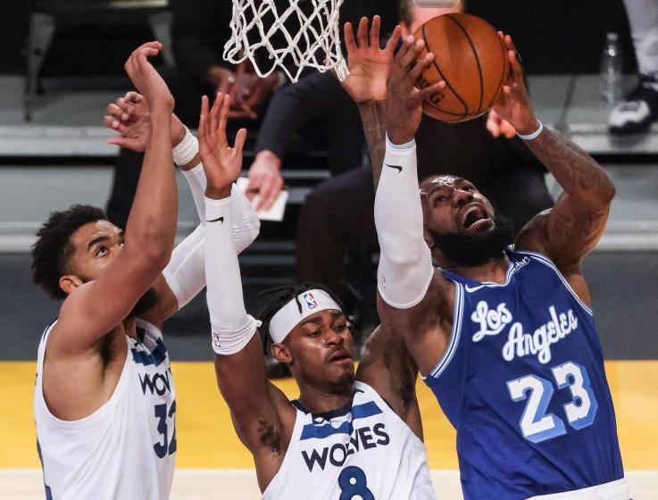 Los Angeles, CA, Tuesday, March 16, 2021 - Los Angeles Lakers forward LeBron James (23) drives past Minnesota Timberwolves forward Jarred Vanderbilt (8) and center Karl-Anthony Towns (32) in the second half at Staples Center. (Robert Gauthier/Los Angeles Times)