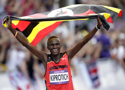 Kiprotich celebrates with his national flag after winning the men's marathon (REUTERS)