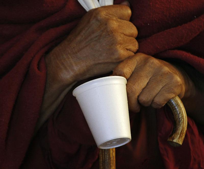 FILE- In this Nov. 30, 2012 file photo, a Tibetan Buddhist monk holds his styrofoam cup as he waits for tea during a religious talk by the Dalai Lama at the Tsuglakhang temple in Dharmsala, India. In an effort to double the city's recycling rate by 2017, New York City Sanitation officials are considering a ban on to-go containers made of polystyrene foam, a material in Styrofoam.  (AP Photo/Ashwini Bhatia, File)