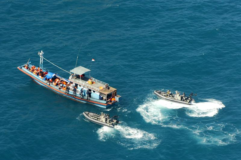 FILE - In this April 29, 2009 file image provided by the Department of Home Affairs, two launches intercept a boat, believed to be carrying 72 suspected asylum seekers, in the Arafura Sea north of the Northern Territory, Australia. New Zealand is proposing new measures to allow  authorities to detain large groups of boat refugees under a single warrant for up to six months. If New Zealand passes the new measures and essentially matches Australia's approach, it is likely to push the problem back onto Australia because New Zealand's larger neighbour remains a closer destination for refugees.(AP Photo/Department of Home Affairs, File) EDITORIAL USE ONLY