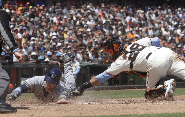 San Francisco Giants catcher Buster Posey (28) tags out Milwaukee Brewers' Yasmani Grandal at home during the third inning of a baseball game in San Francisco, Sunday, June 16, 2019. (AP Photo/Jeff Chiu)