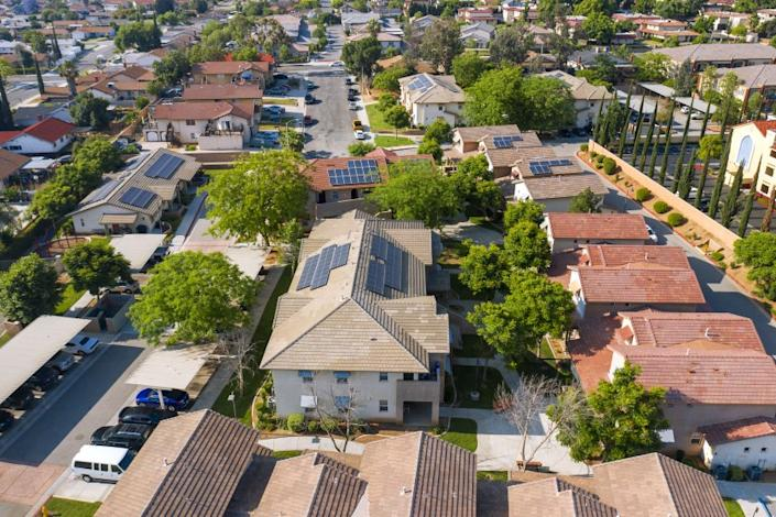 An aerial view of homes with solar panels on their roofs.