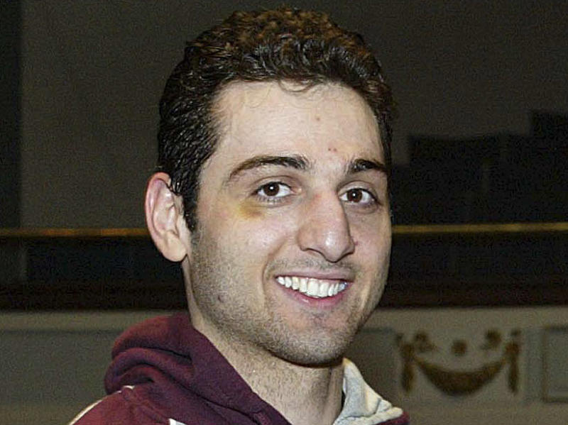 FILE - In this Feb. 17, 2010, photo, Tamerlan Tsarnaev, left, smiles after accepting the trophy for winning the 2010 New England Golden Gloves Championship in Lowell, Mass. Tsarnaev, the older of the brothers suspected in the Boston Marathon bombing, died from gunshot wounds and blunt trauma to his head and torso, his death certificate says. (AP Photo/The Lowell Sun, Julia Malakie, File) MANDATORY CREDIT