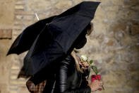 A woman holds an umbrella and a rose during a protest against tightening of Poland's already restrictive abortion law, in front of the Polish Embassy in Rome, Wednesday, Oct. 28, 2020. Poland's constitutional court declared that aborting fetuses with congenital defects is unconstitutional. Poland already had one of Europe's most restrictive abortion laws, and the ruling will result in a near-complete ban on abortion. (Cecilia Fabiano/LaPresse via AP)