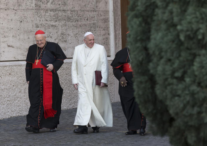 """Pope Francis, flanked by cardinals Angelo Sodano, left, and Laurent Monsengwo Pasinya, as arrives to open the morning session of an extraordinary consistory in the Synod hall at the Vatican, Friday, Feb. 21, 2014. Pope Francis is leading a two-day meeting urging his cardinals to find """"intelligent, courageous"""" ways to help families under threat today without delving into case-by-case options to get around Catholic doctrine. He said the church must find ways to help families with pastoral care that is """"full of love.""""(AP Photo/Alessandra Tarantino)"""