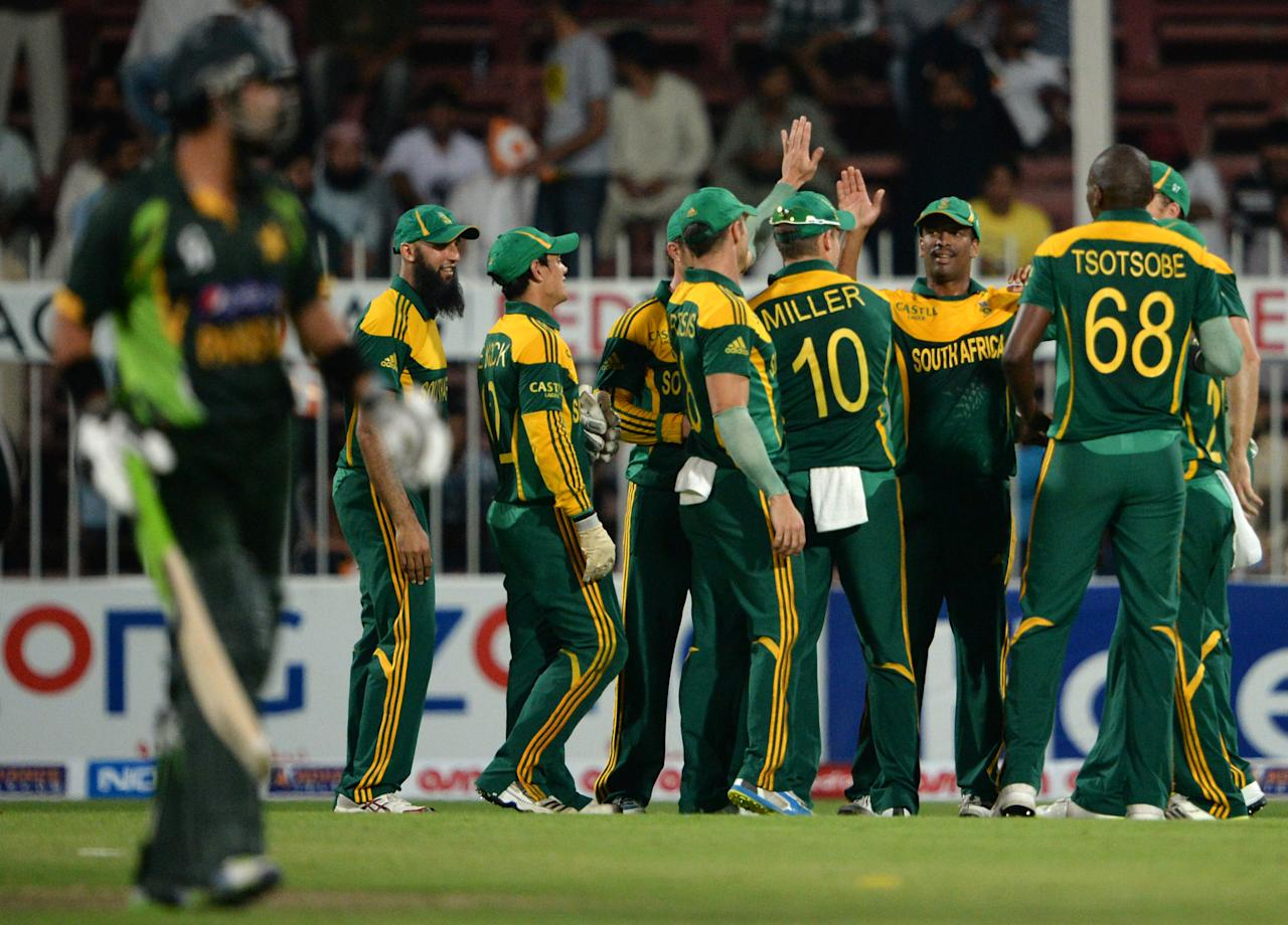 South African cricketers celebrate after taking wicket of Pakistan's opener batsman Ahmad Shehzad (L) during the fifth and final day international at Sharjah Cricket Stadium in Sharjah on November 11, 2013. Pakistan were chasing a challenging 268-run target after South African skipper AB de Villiers samshed a 102-ball 115 not out in his team's 268-7 run total. South Africa lead the five-match series 3-1.  AFP PHOTO/ASIF HASSAN