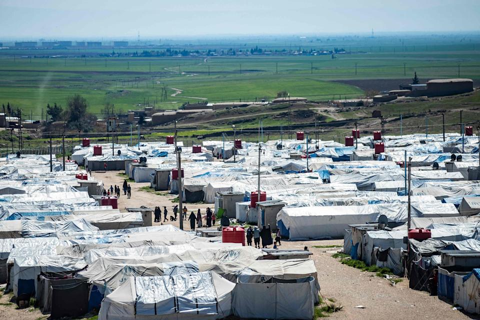 Women and children walk at Camp Roj, where relatives of people suspected of belonging to Isis are held (AFP via Getty Images)