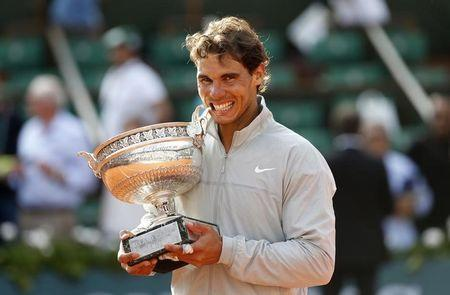 Rafael Nadal of Spain poses with the trophy during the ceremony after defeating Novak Djokovic of Serbia during their men's singles final match to win the French Open Tennis tournament at the Roland Garros stadium in Paris June 8, 2014. REUTERS/Vincent Kessler