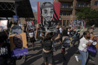 Protestors carry images of people fatally shot by police, as they march, after former Minneapolis police officer Derek Chauvin was sentenced to 22.5 years in prison for the murder of George Floyd, Friday, June 25, 2021, in downtown Minneapolis. Floyd family members and others said they were disappointed the sentence wasn't longer, even as legal experts and others pointed out that it is extremely rare for a police officer to be prosecuted, convicted and handed a prison term that heavy.(AP Photo/Julio Cortez)