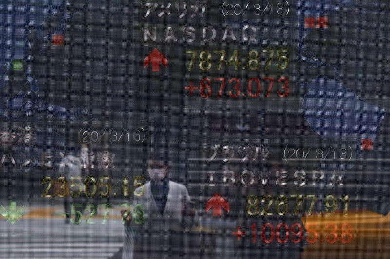 A woman wearing a protective face mask, following an outbreak of the coronavirus disease (COVID-19), is reflected in a screen displaying NASDAQ movements outside a brokerage in Tokyo