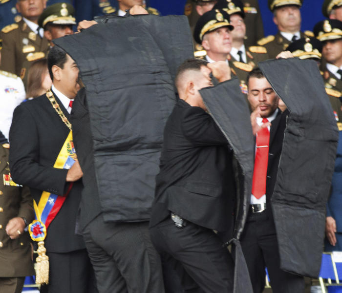 In this photo released by China's Xinhua News Agency, security personnel surround Venezuela's President Nicolas Maduro, at left, during an incident as he was giving a speech in Caracas, Venezuela, Saturday, Aug. 4, 2018. Drones armed with explosives detonated near Venezuelan President Nicolas Maduro as he gave a speech to hundreds of soldiers in Caracas on Saturday but the socialist leader was unharmed, according to the government. (Xinhua via AP)
