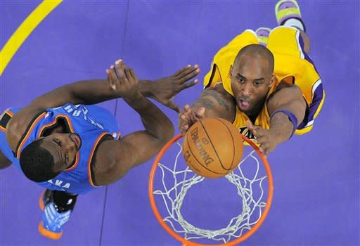 Los Angeles Lakers guard Kobe Bryant, right, puts up a shot as Oklahoma City Thunder forward Serge Ibaka defends during the first half in Game 4 of an NBA basketball playoffs Western Conference semifinal, Saturday, May 19, 2012, in Los Angeles. (AP Photo/Mark J. Terrill)