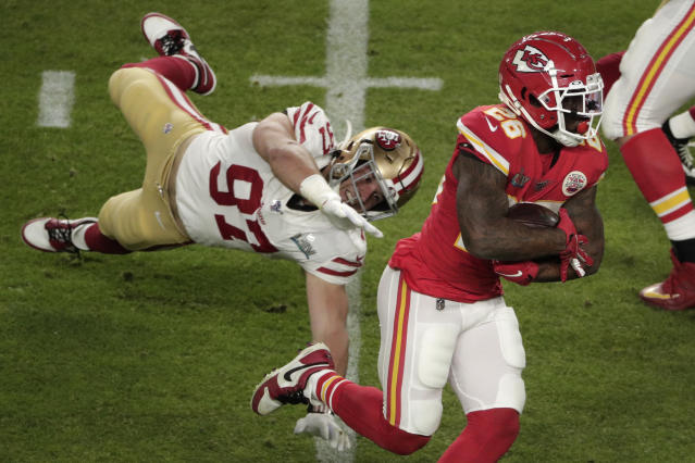 Kansas City Chiefs' Damien Williams (26) runs ahead of a tackle by San Francisco 49ers' Nick Bosa (97), during the first half of the NFL Super Bowl 54 football game Sunday, Feb. 2, 2020, in Miami Gardens, Fla. (AP Photo/Charlie Riedel)