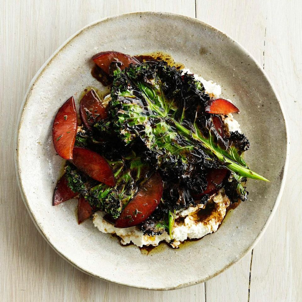 """Quickly grilling kale makes it crispy. Pairing it with fresh plums and ricotta transforms it into our new favorite salad. <a href=""""https://www.epicurious.com/recipes/food/views/grilled-kale-salad-with-ricotta-and-plums-51104400?mbid=synd_yahoo_rss"""" rel=""""nofollow noopener"""" target=""""_blank"""" data-ylk=""""slk:See recipe."""" class=""""link rapid-noclick-resp"""">See recipe.</a>"""