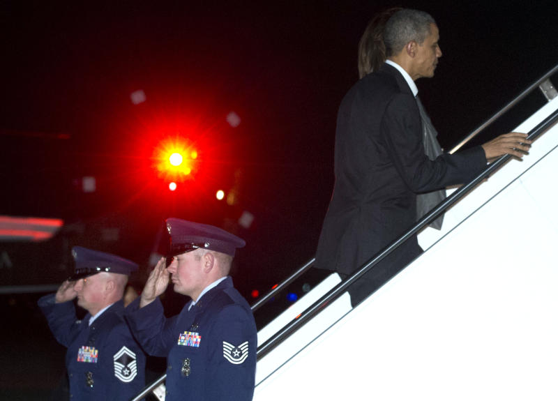 President Barack Obama and first lady Michelle Obama board Air Force One, Friday, Dec. 20, 2013, in Andrews Air Force Base, Md., en route to Hawaii for their annual family vacation. (AP Photo/Carolyn Kaster)