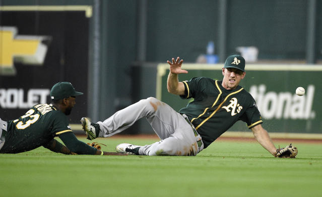 Oakland Athletics right fielder Stephen Piscotty, right, and second baseman Jurickson Profar miss a fly ball by Houston Astros' George Springer, who ended up with a double during the eighth inning of a baseball game Sunday, April 7, 2019, in Houston. (AP Photo/Eric Christian Smith)