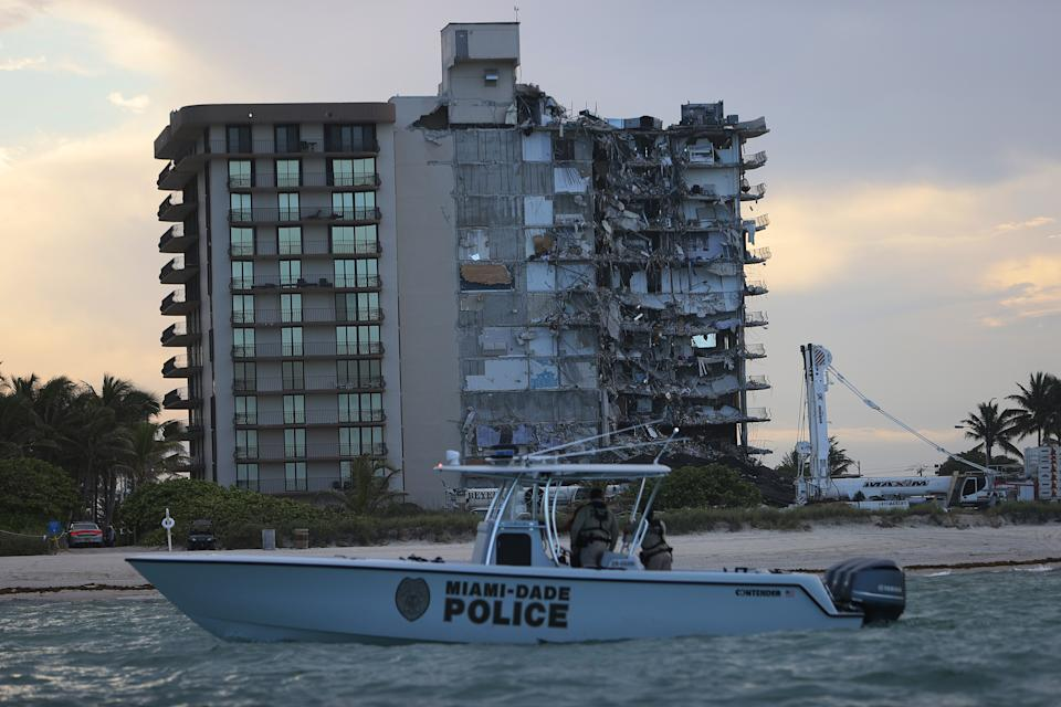SURFSIDE, FLORIDA - JULY 04: A police boat passes off shore of the partially collapsed 12-story Champlain Towers South condo building before a controlled demolition on July 4, 2021 in Surfside, Florida. The decision by officials to bring the rest of the building down was brought on by the approach of Tropical Storm Elsa and fears that the structure might come down in an uncontrolled fashion. Over one hundred people are missing as the search-and-rescue effort continues. (Photo by Joe Raedle/Getty Images)