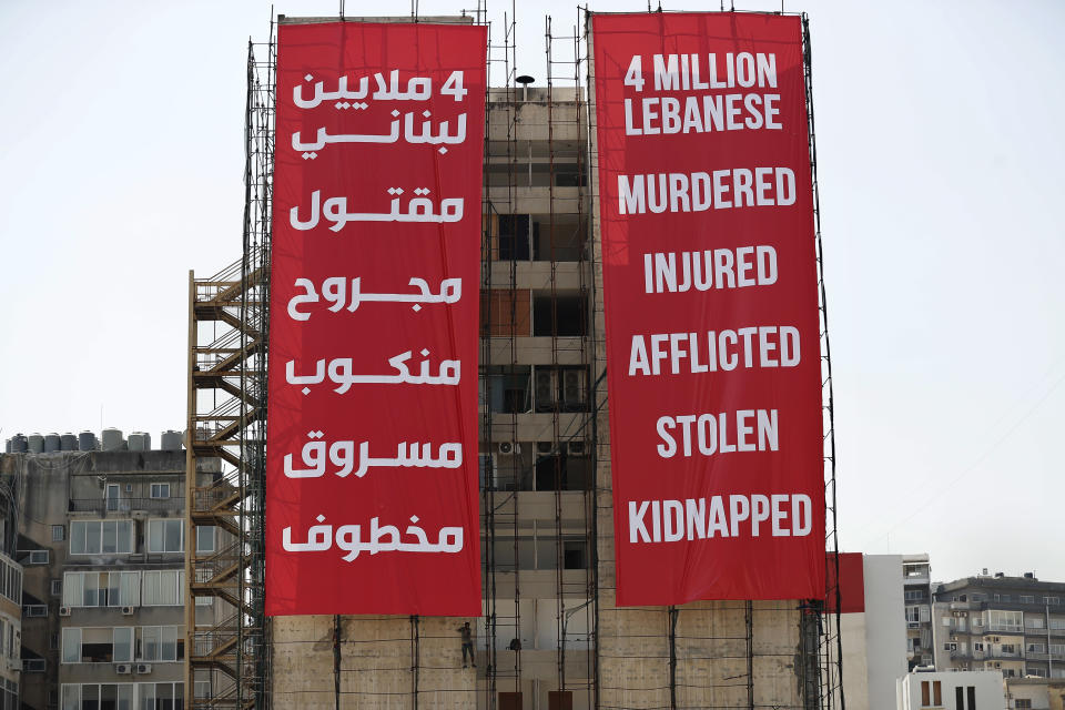 Workers set giant banners on a building that was damaged during last year's massive seaport explosion during a commemoration in Beirut, Lebanon, Wednesday, Aug. 4, 2021. Lebanon is marking one year since the horrific explosion at Beirut port. The grim anniversary Wednesday comes amid an unprecedented economic and financial meltdown and a political stalemate that has kept the country without a functioning government for a full year. (AP Photo/Hussein Malla)