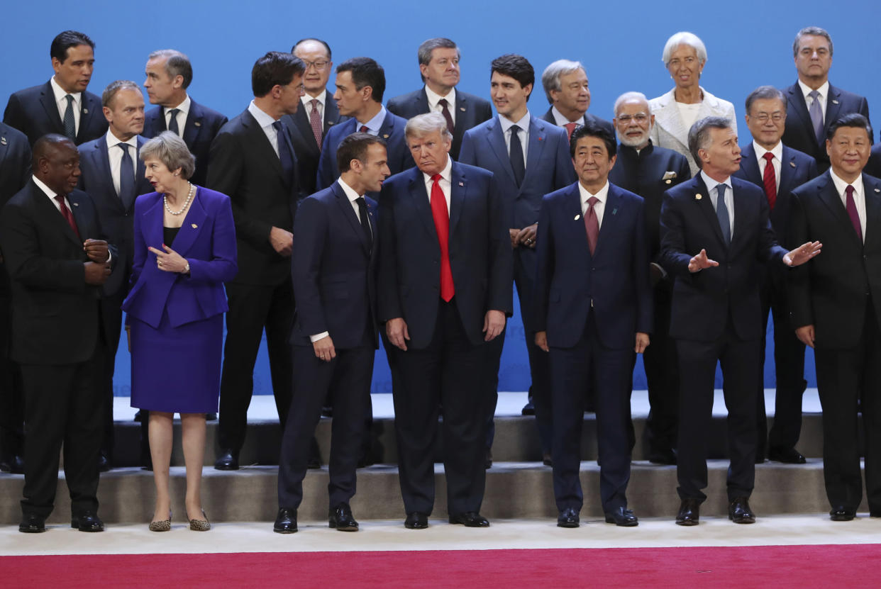 President Donald Trump, front center, listens to France's President Emmanuel Macron as they pose with world leaders for a group picture at the start of the G-20 Leader's Summit inside the Costa Salguero Center in Buenos Aires, Argentina, Friday, Nov. 30, 2018. Bottom row from left are South Africa's President Cyril Ramaphosa, Britain's Prime Minister Theresa May, Japan's Prime Minister Shinzo Abe, Argentina's President Mauricio Macri and China's President Xi Jinping. Middle row, from left, are European Council's President Donald Tusk, the Netherlands' Prime Minister Mark Rutte, Spain's Prime Minister Pedro Sanchez, France's President Emmanuel Macron, India's Prime Minister Narendra Modi and South Korea's President Moon Jae-in. International Monetary Fund Managing Director Christine Lagarde stands in the top row, second from right. (Photo: Ricardo Mazalan/AP)