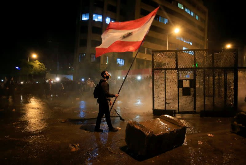 A demonstrator holds the Lebanese flag during a protest against the newly formed government outside the government headquarters in downtown Beirut