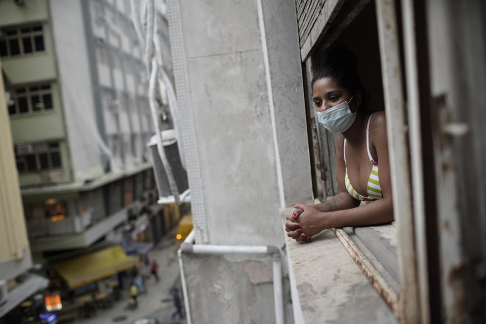 Actress Kelly Regina da Silva looks out from the window of her room in a building occupied by squatters in Rio de Janeiro, Brazil, Tuesday, March 16, 2021. Before the coronavirus pandemic hit da Silva had made it out of her working-class favela and landed a leading role in a play showing right across from Ipanema beach. (AP Photo/Silvia Izquierdo)