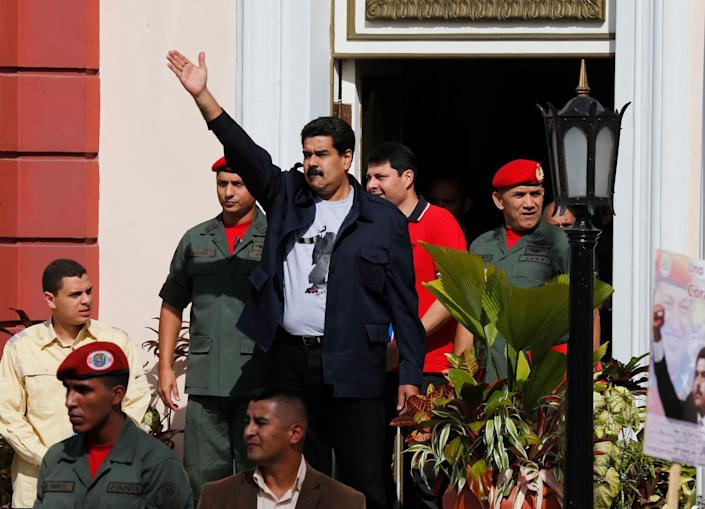 Venezuela's President Nicolas Maduro, center, greets supporters upon his arrival for a rally outside the Miraflores Presidential Palace in Caracas, Venezuela, Saturday, Feb. 22, 2014. Venezuelans on both sides of the nation's political divide took to the streets on Saturday after nearly two weeks of mass protests that have Maduro scrambling to reassert his leadership of this bitterly divided country. (AP Photo/Fernando Llano)