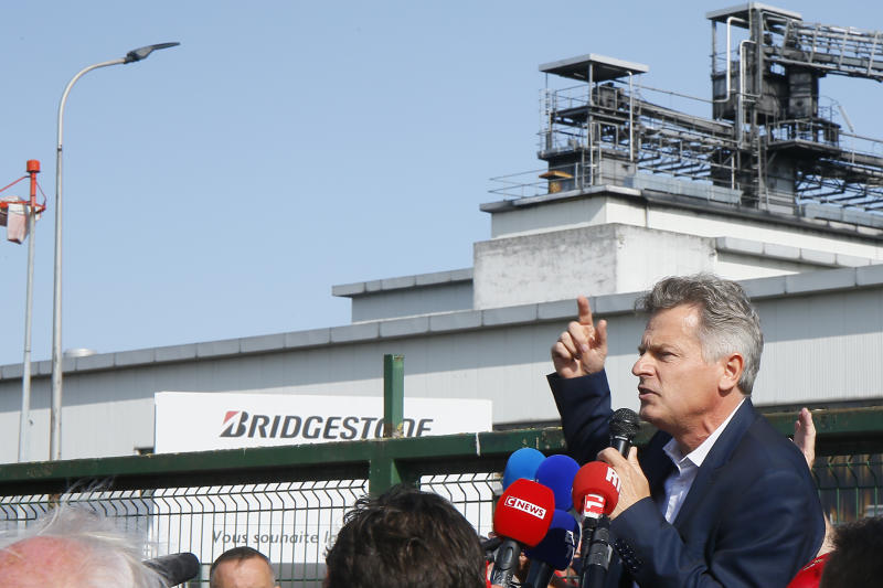 Communist party parliament member Fabien Roussel addresses Bridgestone employees outside the tire factory of Bethune, northern France, Thursday, Sept.17, 2020. Workers protest over the Japan-based company's decision to close the plant and lay off all its nearly 900 workers. Bridgestone argues the factory is no longer competitive globally, but unions and French politicians accused the company of using the virus-driven economic crisis as a pretext for the closure and not investing in modernizing the plant instead. (AP Photo/Michel Spingler)