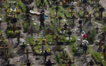 "A musician walks through the municipal cemetery Valle de Chalco amid the new coronavirus pandemic, on the outskirts of Mexico City, Tuesday, Oct. 20, 2020. Mexican families traditionally flock to local cemeteries to honor their dead relatives as part of the ""Dia de los Muertos,"" or Day of the Dead celebrations, but according to authorities the cemeteries will be closed this year to help curb the spread of COVID-19. (AP Photo/Marco Ugarte)"