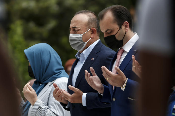 """Turkish Foreign Minister Mevlut Cavusoglu, center, prays over the grave of Ahmet Sadik, who was an MP at the Greek parliament, at a muslim cemetery at Komotini town, in northeastern Greece, Sunday, May 30, 2021. Greece's prime minister said Friday his country is seeking improved ties with neighbor and longtime foe Turkey, but that the onus is on Turkey to refrain from what he called """"provocations, illegal actions and aggressive rhetoric."""" (AP Photo/Giannis Papanikos)"""