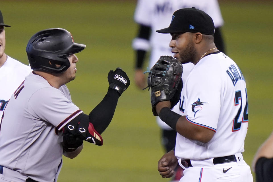 Arizona Diamondbacks' Asdrubal Cabrera, left talks with Miami Marlins first baseman Jesus Aguilar (24) after hitting a double during the first inning of a baseball game, Tuesday, May 4, 2021, in Miami. (AP Photo/Lynne Sladky)
