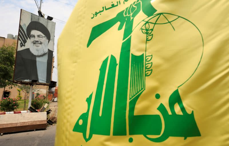 A Hezbollah flag and a poster depicting Lebanon's Hezbollah leader Sayyed Hassan Nasrallah are pictured along a street, near Sidon