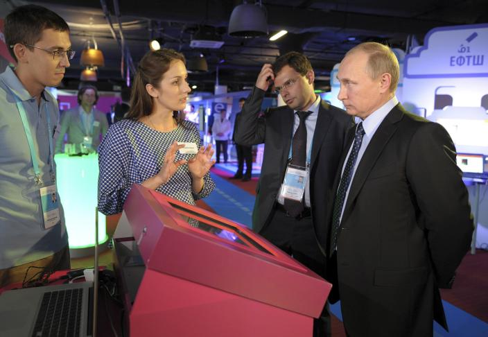 Russia's President Vladimir Putin (R) listens to explanations as he attends an exhibition on internet projects, part of a forum dedicated to internet entrepreneurial business, in Moscow, June 10, 2014. Putin said on Tuesday a fight against illegal content on the Internet should not become a fight against freedom, seeking to calm fears over a possible clampdown on media and social networking sites. REUTERS/Alexei Druzhinin/RIA Novosti/Kremlin (RUSSIA - Tags: POLITICS SCIENCE TECHNOLOGY BUSINESS) ATTENTION EDITORS - DISTRIBUTED, EXACTLY AS RECEIVED BY REUTERS, AS A SERVICE TO CLIENTS. THIS IMAGE HAS BEEN SUPPLIED BY A THIRD PARTY. IT IS DISTRIBUTED, EXACTLY AS RECEIVED BY REUTERS, AS A SERVICE TO CLIENTS