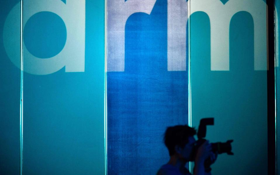 A photographer taking pictures in front of the logo for British chip designer ARM in Taipei.