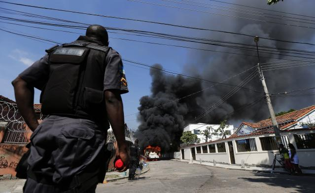 Policemen stand near a burning bus set on fire by residents of the Telerj slum as police attempt to repossess the land in Rio de Janeiro, April 11, 2014. About 5,000 people were evicted by the police after they occupied the site, which belongs to telecoms group Oi, since March 31. REUTERS/Sergio Moraes (BRAZIL - Tags: CIVIL UNREST SOCIETY POVERTY)
