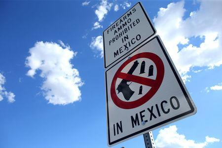 A sign warning drivers that firearms and ammunition are prohibited in Mexico is seen at the U.S.-Mexico border in Nogales, Arizona, United States, October 9, 2016. REUTERS/Mike Blake