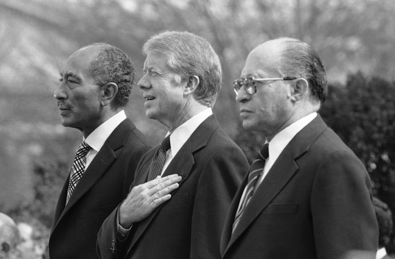 FILE - In this Monday, Feb. 24, 1979 file photo, Egyptian President Anwar Sadat, left, U.S. President Jimmy Carter, center, and Israeli Prime Minister Menachem Begin, stand at attention as the national anthems of their respective countries are played on the north lawn of the White House in Washington. The Central Intelligence Agency has declassified 1,400 pages of intelligence surrounding the Camp David Accords, the historic peace treaty negotiated in 1978 by then-President Jimmy Carter with the leaders of Israel and Egypt, Wednesday, Nov. 13, 2013. (AP Photo/File)