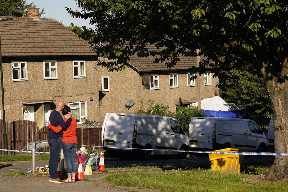 The father to some of the victims leaves flowers at the scene in Chandos Crescent, Killamarsh, near Sheffield, where four people were found dead at a house on Sunday (Danny Lawson/PA) (PA Wire)