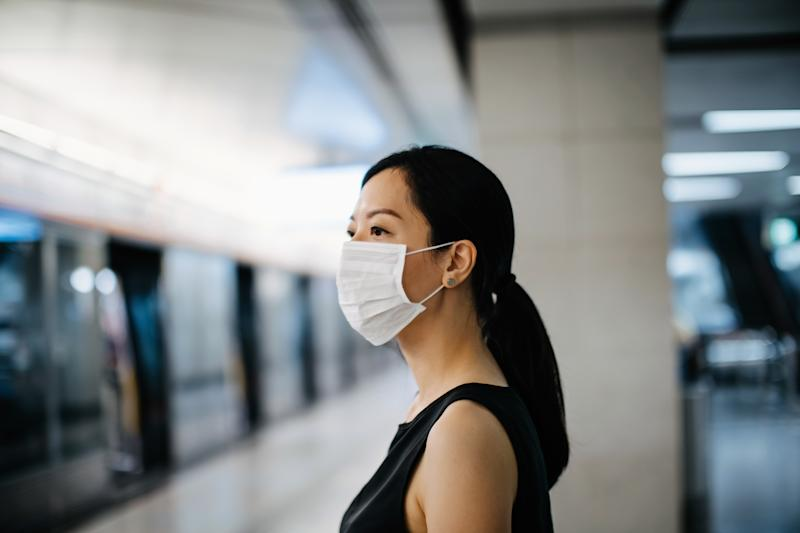 Asian woman with protective face mask waiting for subway MTR train in platform