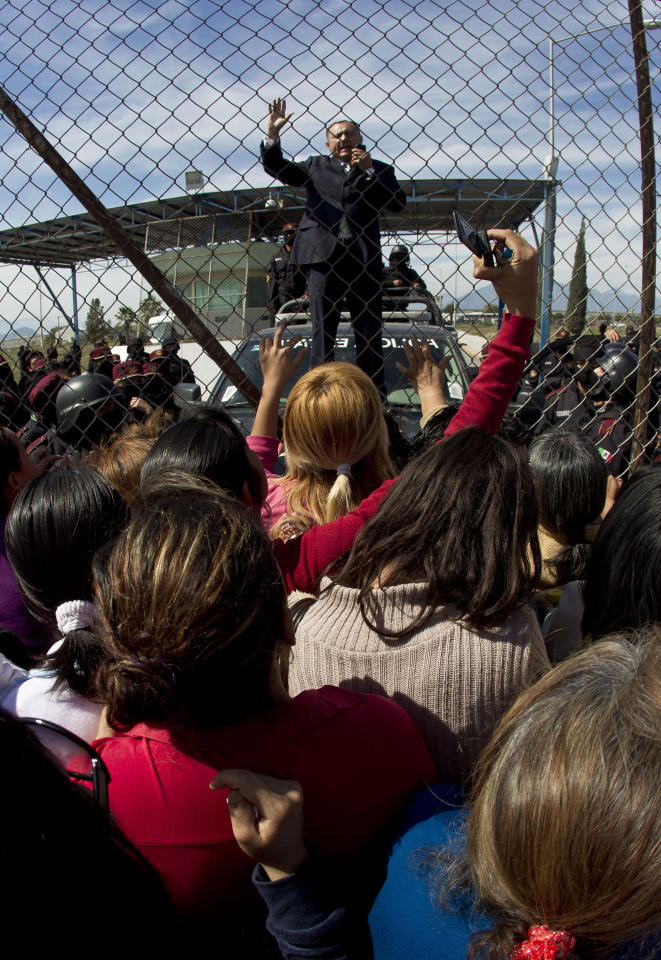 The warden of Apodaca correctional state facility, Filiberto Cecena, briefs the relatives of inmates standing on the other side of a gate as he stands on the hood of a patrol car in Apodaca on the outskirts of Monterrey, Mexico, Sunday Feb. 19, 2012. A fight among inmates at the prison led to a riot that killed dozens on Sunday, according to a security official. (AP Photo/Hans Maximo Musielik)