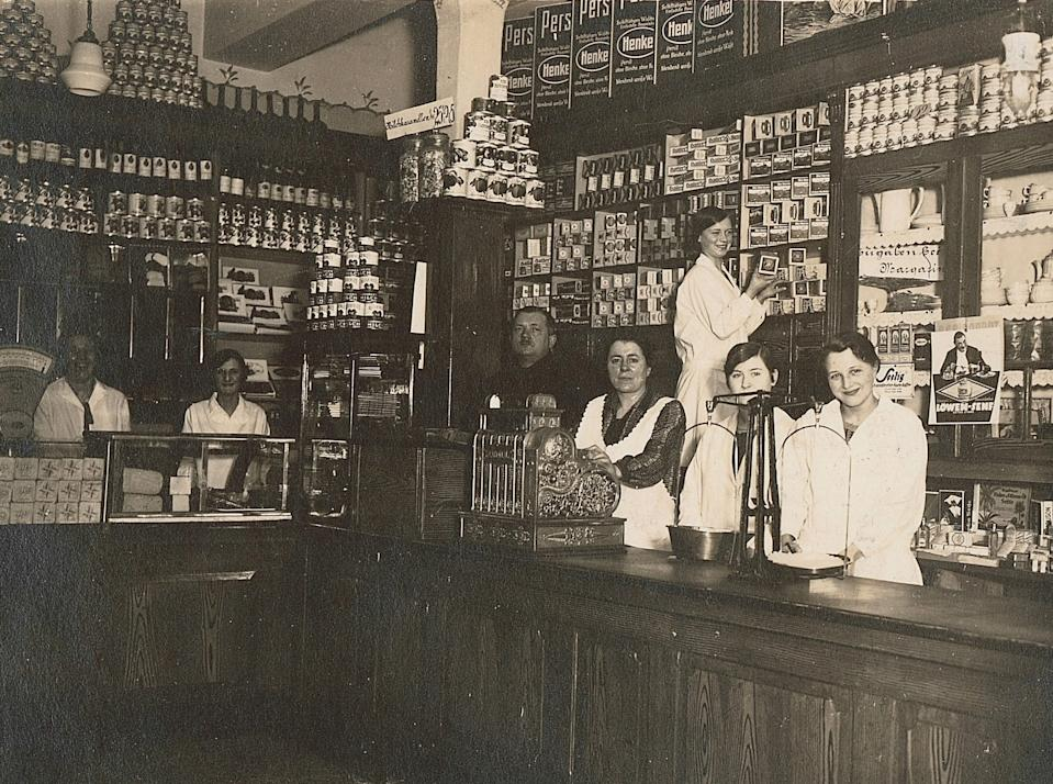Aldi's history: Inside the family's store in 1930 with workers standing behind the wooden counter.