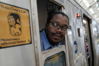 Desmond Hill, a vaccinated MTA conductor, checks the platform for late riders attempting to board the train as he works the N subway line from Brooklyn's Coney Island to Queen's Astoria-Ditmars neighborhoods, Friday, Aug. 13, 2021, in New York. As New York City recovers from the COVID-19 pandemics' peak ridership on the aging transit system continues to rebound as authorities encourage mask and social distancing protocols to stem further transmission of the virus. (AP Photo/John Minchillo)