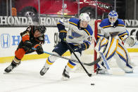 St. Louis Blues defenseman Torey Krug, center, skates with the puck as Anaheim Ducks left wing Sonny Milano, left, reaches in and goaltender Ville Husso watches during the second period of an NHL hockey game Monday, March 1, 2021, in Anaheim, Calif. (AP Photo/Mark J. Terrill)